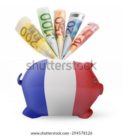 Side view of a piggy bank with the flag design of France and various european banknotes.(series) - stock photo