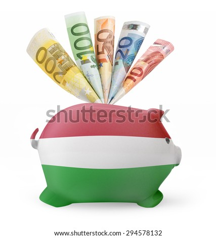 Side view of a piggy bank with the flag design of Hungary and various european banknotes.(series) - stock photo