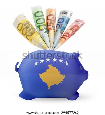 Side view of a piggy bank with the flag design of Kosovo and various european banknotes.(series) - stock photo