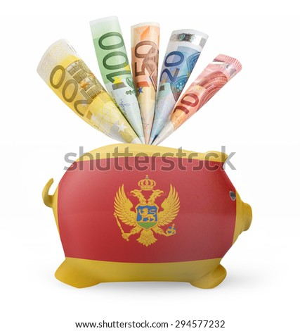 Side view of a piggy bank with the flag design of Montenegro and various european banknotes.(series) - stock photo