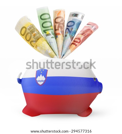Side view of a piggy bank with the flag design of Slovenia and various european banknotes.(series) - stock photo