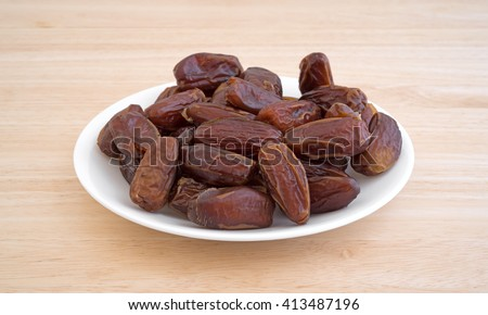 Side view of a plate of Tunisian pitted dates a wood table top. - stock photo