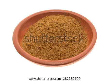 Side view of a portion of ground cinnamon in a small bowl isolated on a white background.