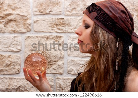 Side view of a pretty female fortune teller - stock photo