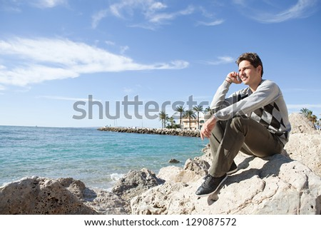 "Side view of a professional man sitting on a rock on the beach having a telephone conversation on his ""smart phone"" during a sunny day. - stock photo"