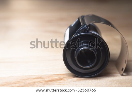 Side view of a roll of photographic camera film in canister, resting  a wooden table. Copy space left frame. - stock photo