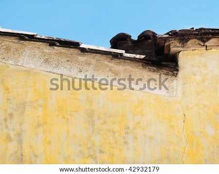 Side view of a roof with yellow vintage wall under blue sky