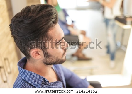side view of a seated young casual man with nice hairstyle, waiting - stock photo