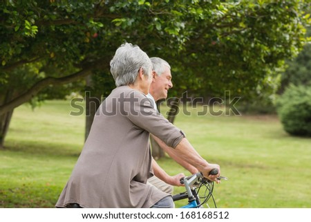 Side view of a senior couple on cycle ride in countryside - stock photo