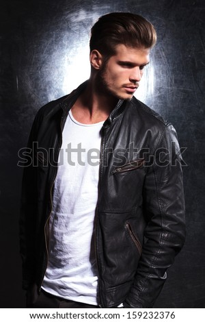 side view of a serious young fashion model in leather jacket looking away from the camera - stock photo