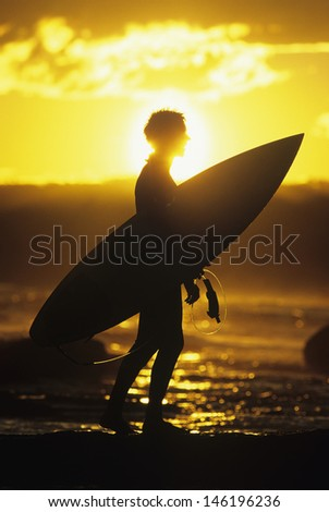 Side view of a silhouette male surfer carrying surfboard along beach at sunset - stock photo