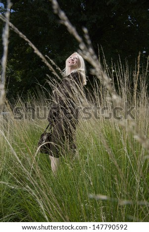 Side view of a smiling middle woman looking up in a Meadow - stock photo
