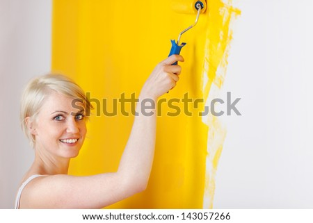 Side view of a smiling young blond woman painting the wall yellow - stock photo