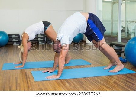Side view of a sporty young couple in bending posture at the fitness studio - stock photo