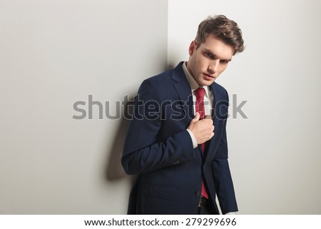 Side view of a successful young business man leaning on a grey wall while fixing his tie.