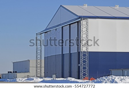 side view of a tall hangar with closed doors