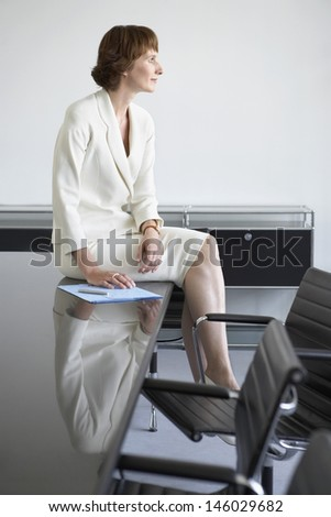 Side view of a thoughtful businesswoman sitting on table in conference room - stock photo