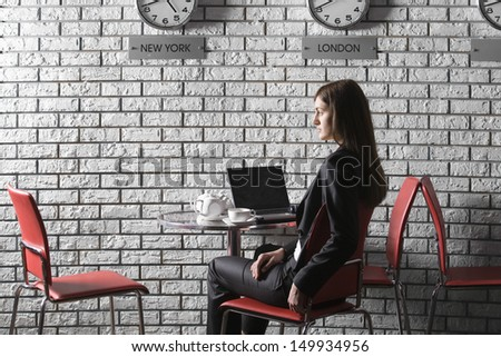 Side view of a thoughtful businesswoman sitting with laptop in cafe - stock photo
