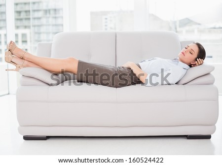 Side view of a well dressed young woman sleeping on sofa at home - stock photo