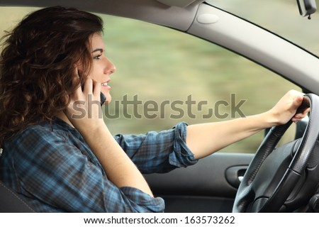 Side view of a woman driving a car and talking on the phone with motion blur           - stock photo
