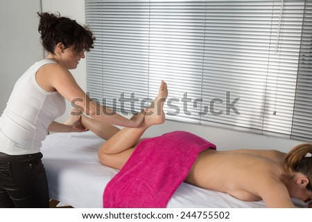 Side view of a woman legs receiving a massage therapy - stock photo