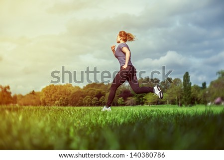 Side view of a woman running on the grass - stock photo