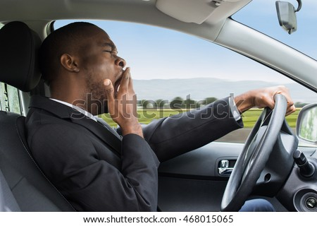 Side View Of A Young African Businessman Yawning While Driving Car