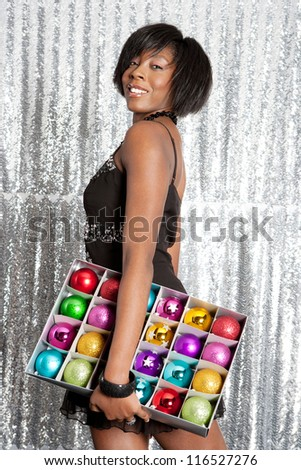 Side view of a young black woman holding a box with different color christmas balls decorations while smiling against a silver sequins background.