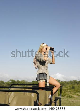 Side view of a young blond woman on safari standing in jeep looking through binoculars - stock photo