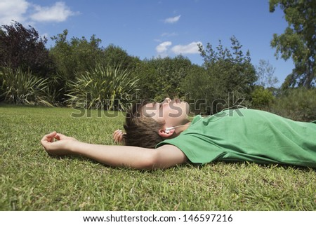 Side view of a young boy resting on grass and listening to MP3 player