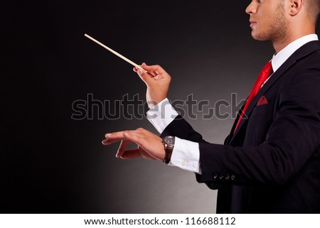 side view of a young business man conducting with a conductor's baton, on a dark background - stock photo