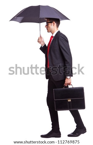 side view of a young business man holding an umbrella and a briefcase