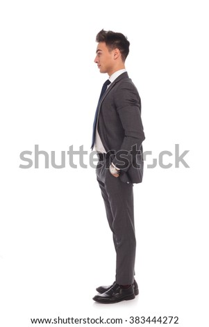 side view of a young business man standing in line with hands in his pockets