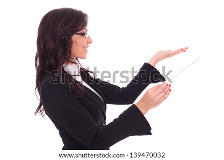 side view of a young business woman holding a conductor's stick and conducting while looking away from the camera and smiling. on white background - stock photo