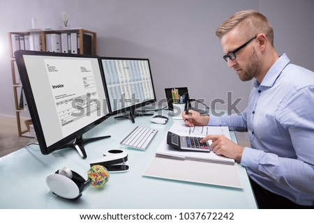 Side View Of A Young Businessman Calculating Invoice With Calculator At Workplace