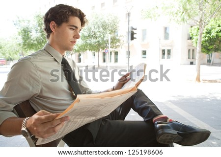 Side view of a young businessman reading a financial newspaper while sitting on a bench in the city, wearing quirky colorful socks.