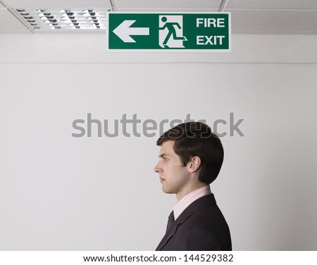 Side view of a young businessman standing under exit sign - stock photo