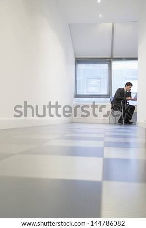 Side view of a young businessman using laptop in an empty room