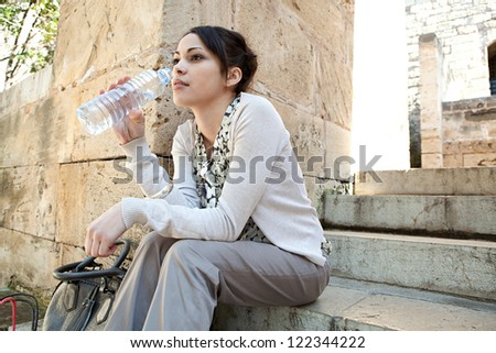 Side view of a young businesswoman sitting on a park steps drinking water from a plastic blue bottle. - stock photo