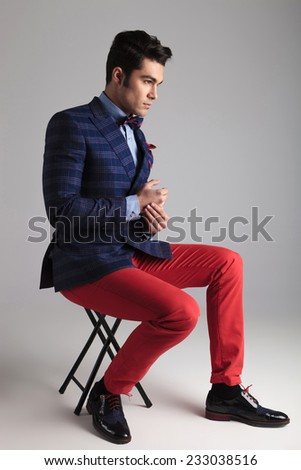 Side view of a young casual man sitting on a stool holding his hands together. - stock photo