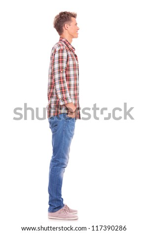 side view of a young casual man standing with his hand in his pockets, looking away from the camera - stock photo