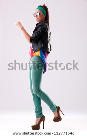 side view of a young casual woman in sunglasses and high heels , stepping forward - stock photo