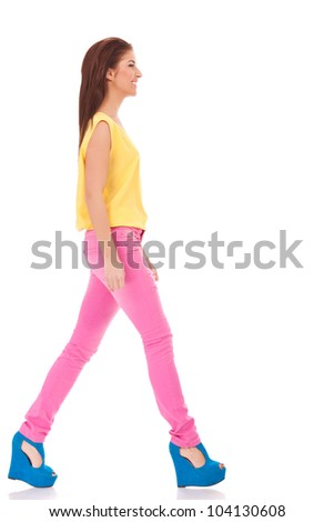 side view of a young casual woman walking on white background
