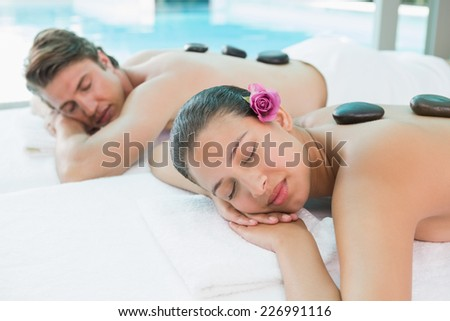 Side view of a young couple enjoying stone massage at health farm - stock photo