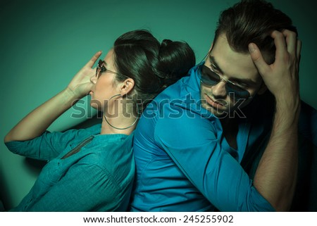Side view of a young fashion couple leaning on each other while looking away from the camera. - stock photo