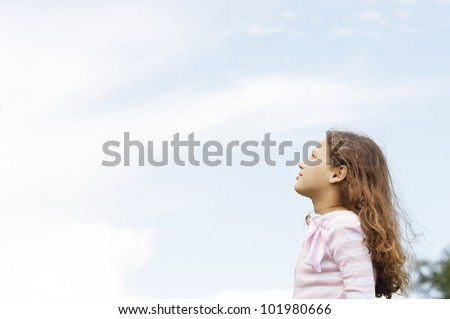 Side view of a young girl looking ahead in the park, against a blue sky background. - stock photo