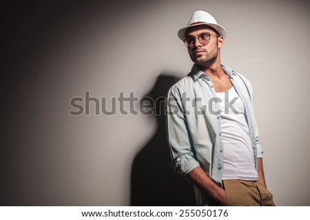 Side view of a young handsome casual man looking away from the camera while holding his hands in pockets. - stock photo