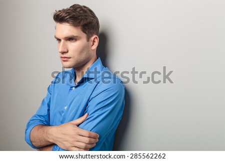 Side view of a young handsome casual man looking away from the camera while leaning on a grey wall. - stock photo