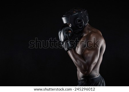 Side view of a young male boxer in a fighting stance on black background. African male boxer blocking his face with gloves. - stock photo