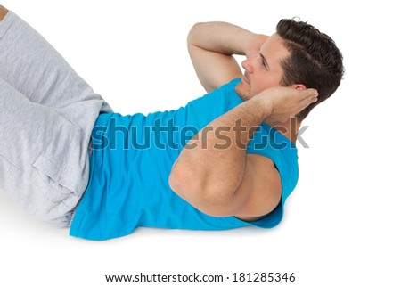 Side view of a young man doing abdominal crunches over white background - stock photo